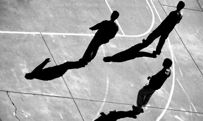 silhouette of young men on basketball pitch